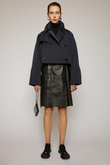 Acne Studios navy/khaki trench coat is crafted from bonded technical cotton to a relaxed shape with raglan sleeves and features a drawstring hem to cinch in the waist.