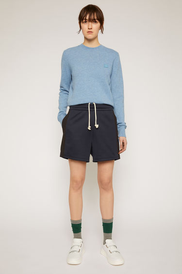 Acne Studios navy blue track shorts are crafted from lustrous technical jersey with an elasticated waist and accented with a face-embroidered patch and contrasting side-stripes.