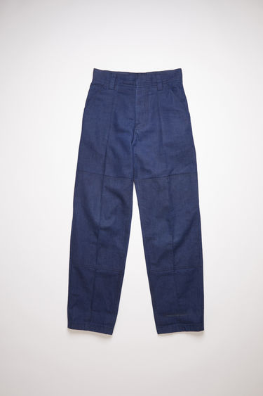 Acne Studios indigo blue classic workwear trousers are made of indigo denim with creased legs and a leather face patch.