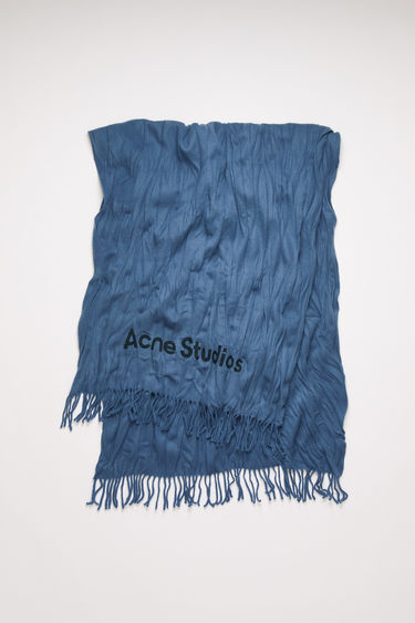 Acne Studios denim blue scarf is crafted to a wide dimension from wool with crinkle effect and features a jacquard logo above the fringed edges.