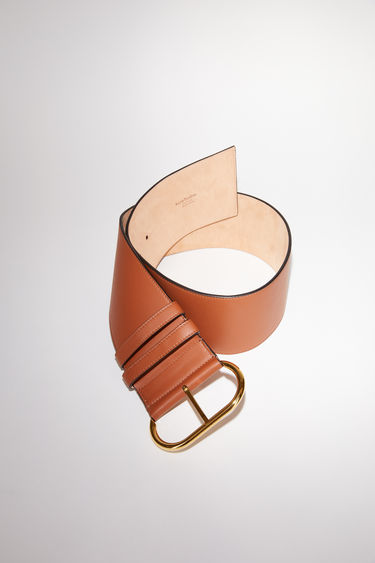 Acne Studios almond brown wide minimalist belt is made of leather and closes with an oval-shaped branded buckle.