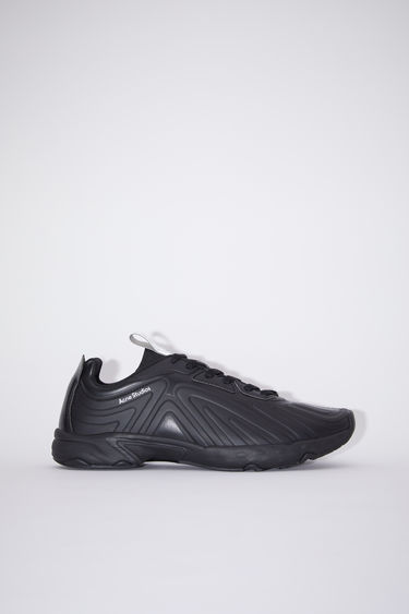 Acne Studios black sneakers feature a combination of running and trail elements in one silhouette. They're crafted from faux leather and features angular ridges on the upper. It's set on a cushioned sole and accented with a pink logo tab on the heel.