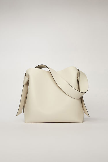 Acne Studios Musubi Midi white/black bag features twisted knots inspired by the formation of traditional Japanese obi sash. It's crafted from soft grain leather and has a central zipped divider to store small essentials.