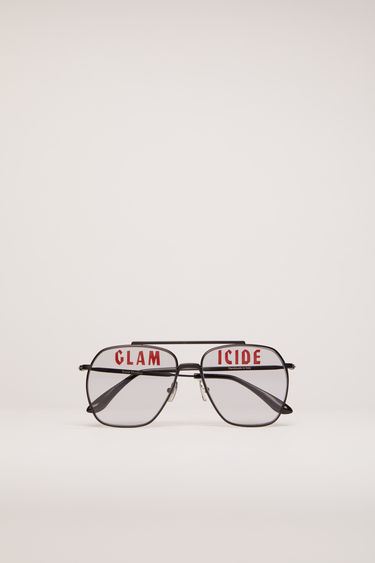 Acne Studios black satin/grey sunglasses are shaped with squared aviator metal frames with a double bridge and then printed with the words 'Glamicide' across the grey tinted lenses.