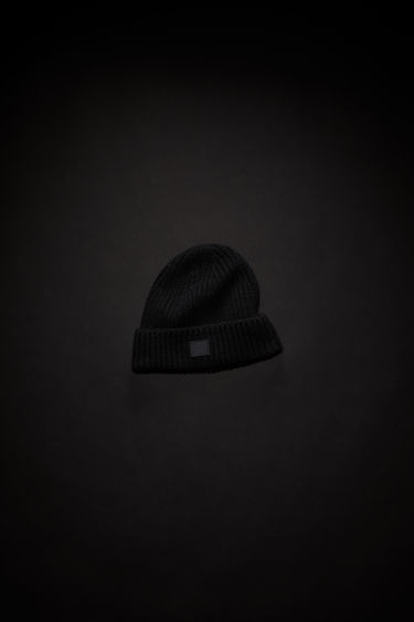 Acne Studios children's black hat is made from rib knit wool with a face logo patch.