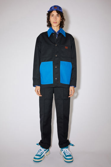 Acne Studios black/royal blue unlined workwear jacket is made of crisp cotton twill with contrasting details and a face logo patch.