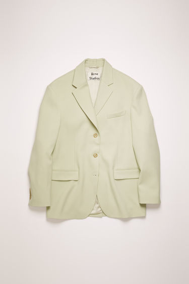 Acne Studios pastel green jacket is cut to an oversized fit with dropped shoulder seams and finished with a single-breasted buttoned front and an adjustable back belt.