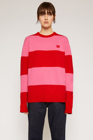 Acne Studios red/bubblegum pink wool sweater is knitted in a relaxed shape with block stripes and accented with a face-embroidered patch on the chest.