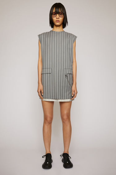 Acne Studios light grey dress is crafted to a boxy silhouette from two different pinstripe suitings and features two front flap pockets with a silver-tone chain.