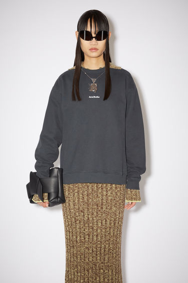 Acne Studios black sweatshirt is made from pigment-dyed jersey that's lightly faded along the seams. It's cut to a relaxed silhouette with dropped shoulders and features a raised logo print on front.