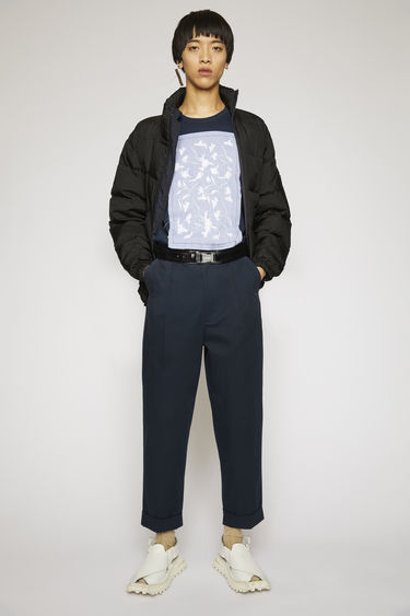 Acne Studios navy cotton trousers are cut to tapered legs with a pleated front and finished with fixed turn-up hems.