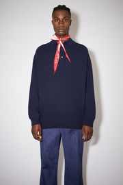 Acne Studios navy long sleeve polo sweater is made of lambswool with rib knit details at the cuffs and hem.