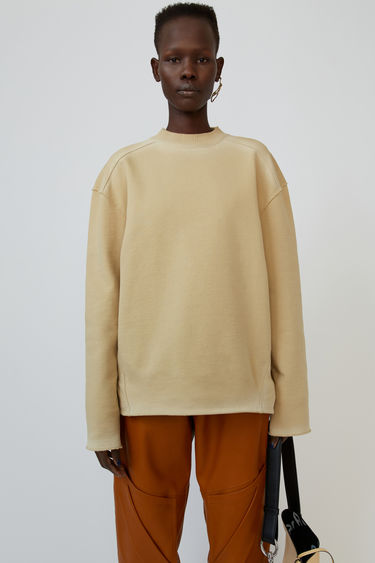 Acne Studios wheat beige sweatshirt is crafted from cotton fleece and finished with raw-edged trims and faded marks for a worn-in look.