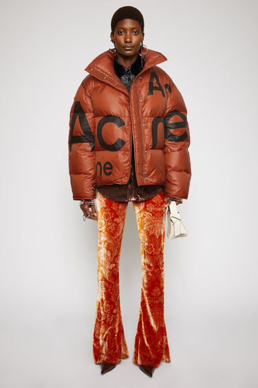 Acne Studios rust orange down jacket is crafted to a cocoon shape with a packaway hood, drawstring hem and features a black logo print on the front and back.