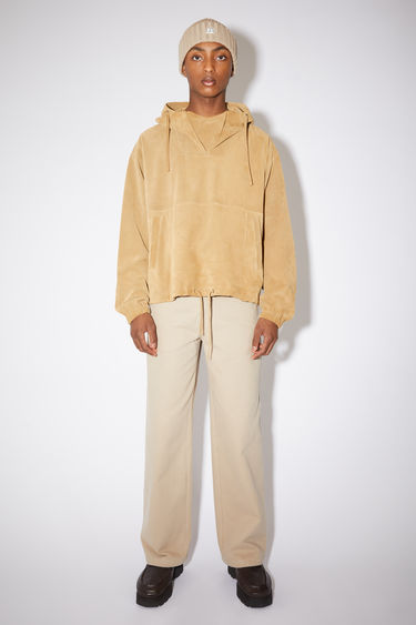 Acne Studios mushroom beige hooded pullover jacket is made of suede with a relaxed fit.