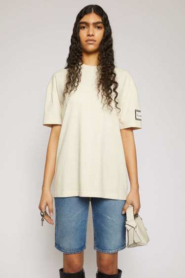 Acne Studios warm white t-shirt is crafted from organic cotton to an oversized silhouette and adorned with a label patch on the sleeve.