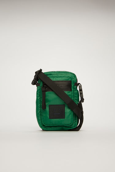 Acne Studios green/black phone wallet is made from technical ripstop and equipped with zipped pockets and a detachable webbing strap.