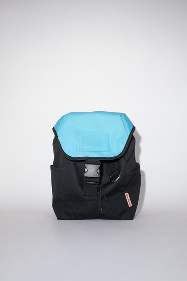 Acne Studios black/blue durable backpack has a clear vinyl ID pocket, two generous side pockets, adjustable straps, and an Acne Studios logo tab.
