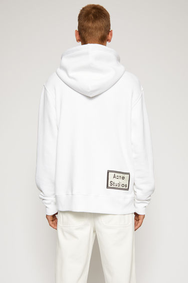 Acne Studios optic white hooded sweatshirt is crafted from loopback jersey and features a reversed label patch at the lower back.