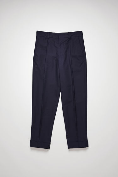 Acne Studios navy trousers are made from lightweight cotton twill and cut to a cropped, tapered leg and neatly finished with front pleats and cuffed hems.