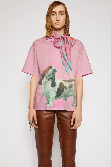 Acne Studios pink shirt is cut to a boxy silhouette with an open collar and short sleeves and features a prize dog print created by British artist Lydia Blakeley.