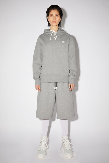 Acne Studios grey melange regular fit hooded sweatshirt is made of organic cotton with an embroidered face and ribbed details.