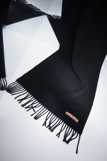 Acne Studios black narrow fringed scarf is made of pure wool, featuring a label in one corner.
