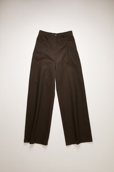 Acne Studios chestnut brown twill trousers take cues from men's workwear garments. They're tailored in a wide-leg shape that drapes loosely over the leg and designed with a traditional five-pocket design.