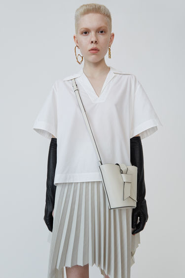 Acne Studios white boxy, cropped shirt with short sleeves.