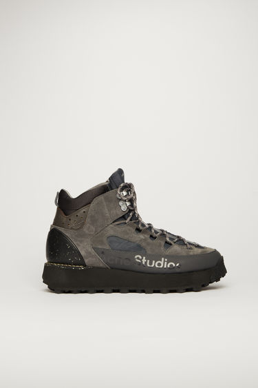 Acne Studios slate grey boots take cues from functional elements of hiking gears. They're crafted with faux suede and mesh overlays accented with rope-style laces and metal lace clasps, then set on a lug sole.