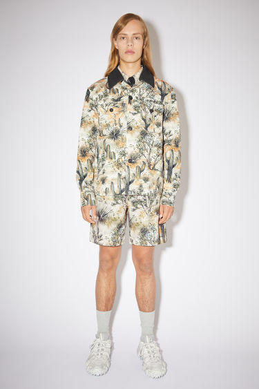 Acne Studios desert beige casual workwear jacket is made of printed cotton with two button chest pockets.