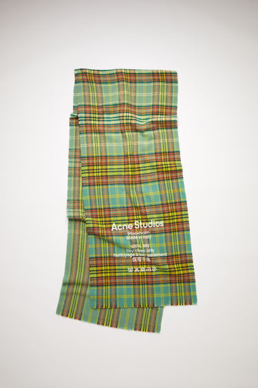 Acne Studios dusty green/rust orange narrow, tartan check scarf is made of wool with a large, printed care label.