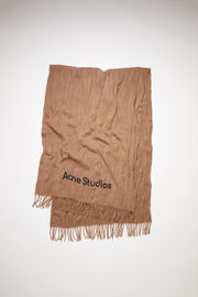 Acne Studios caramel brown oversized fringed scarf is made of crinkled wool, featuring a printed logo.