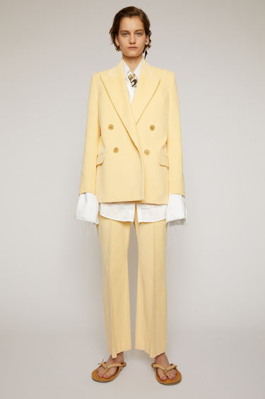Acne Studios vanilla yellow corduroy suit jacket is crafted to a double-breasted silhouette and finished with wide notch lapels and two front flap pockets.