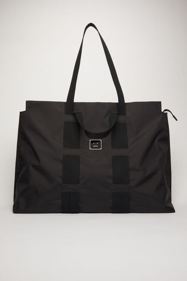 Acne Studios black tote bag is crafted from technical ripstop and features two different cotton-canvas handles that's woven on the body of the bag. It's finished with a zip-top fastening that opens to reveal a spacious interior with a mesh pocket and key ring.