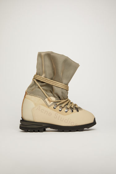 Acne Studios sand beige boots are reinterpreted from the trekking footwear from the 90's. They are constructed with a layered upper and set on a lug-sole.