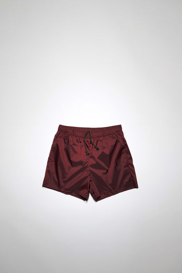 Acne Studios burgundy swim shorts are crafted from technical nylon with front and back pockets and finished with an elasticated waistband with round drawstrings.