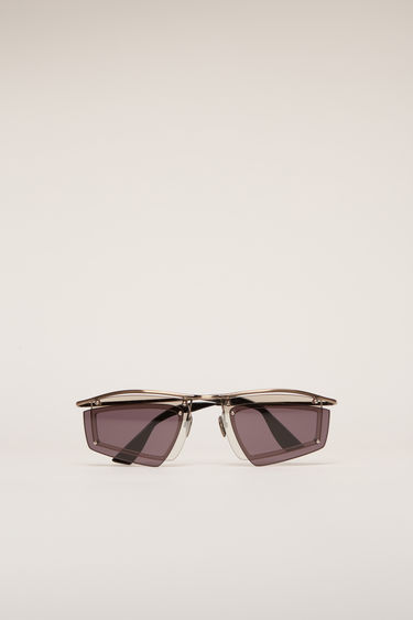 Acne Studios gold/burgundy sunglasses are crafted with a shield metal frame set with a double-layered tinted lenses and then finished with discreet logo lettering at the temple.