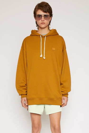 Acne Studios caramel brown hooded sweatshirt is crafted from midweight loopback fleece to an oversized fit and finished with a tonal face patch on the chest.