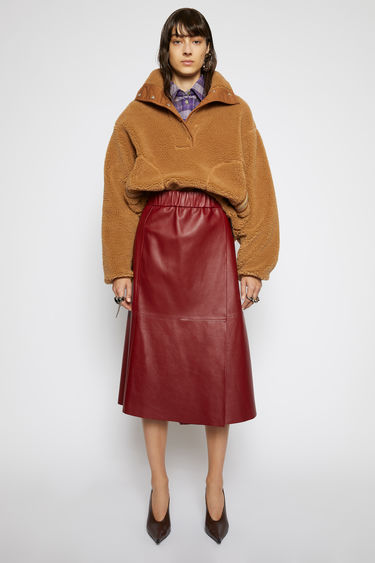 Acne Studios wine red skirt is crafted from soft lamb leather to a wrap-around shape that secures with a velcro strap closure and features a high-rise elasticated waistband.