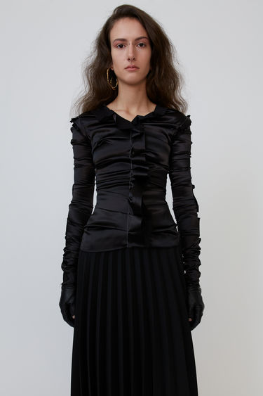 Acne Studios black blouse is crafted from satin and features ruffled trims along the front and sleeves.