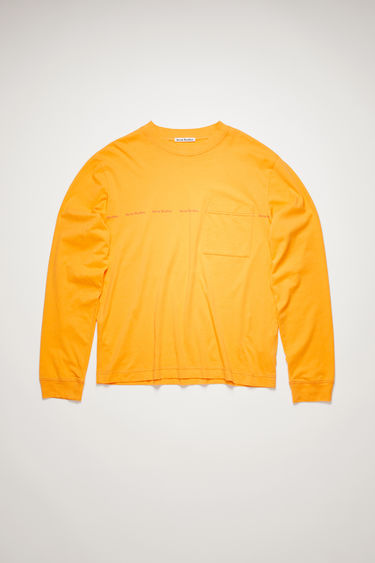 Acne Studios peach orange t-shirt is crafted from organically grown cotton to a relaxed silhouette with a front patch pocket and long sleeves and is stamped with the house's logo across the chest.