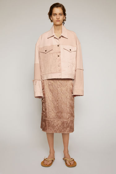 Acne Studios dusty pink jacket is handcrafted in a patchwork pattern from deadstock denim and finished with raw edges along the seams. It's cut in a boxy silhouette with dropped shoulders and finished with buttoned patch pockets.