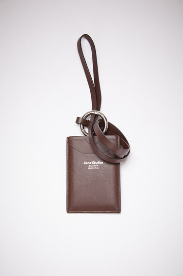Acne Studios dark brown lanyard card holder is made of smooth leather with two card slots and a silver stamped logo on the front.
