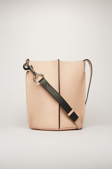 Acne Studios dusty pink bucket bag is crafted from soft grained leather with a logo-debossed leather lining and features an adjustable shoulder strap and a detachable zip wallet.
