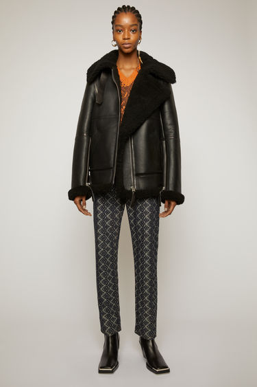 Acne Studios black slightly oversized, boxy shearling jacket inspired by a classic aviator style.