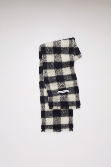 Acne Studios white/black scarf is spun from a blend of alpaca, wool and mohair yarns in a relaxed long-length silhouette that drapes through the body. It's finished with a soft, brushed texture and a logo patch above the fringed edges.