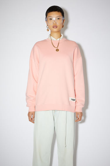Acne Studios salmon pink crew neck sweatshirt is made of a cotton blend with an Acne Studios label on the lower front.