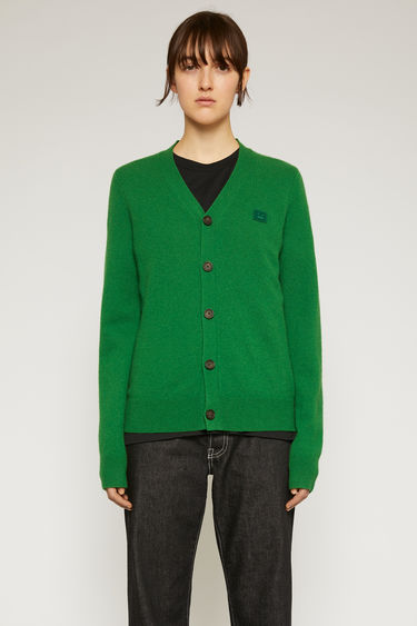 Acne Studios deep green cardigan is knitted with a fine gauge from soft wool yarns and accented with a tonal face-embroidered patch on the chest.