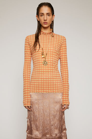 Acne Studios carrot orange top is crafted from lightweight stretch jersey and features the seasonal checked pattern. It's shaped with a crew neck and long sleeves and is purposefully left with loose hanging threads at the hem.